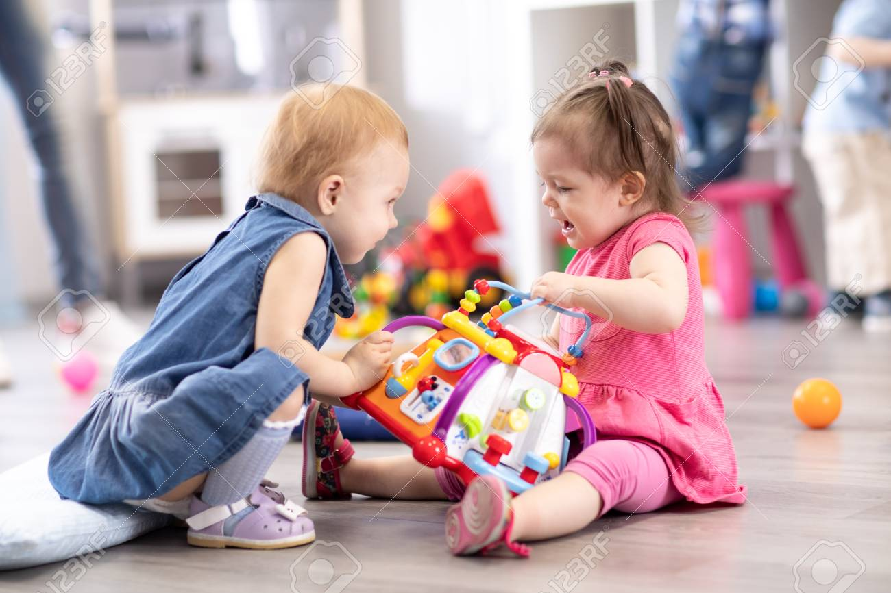 Conflict on the playground. Two kids fighting over a toy in kindergarten - 121461920