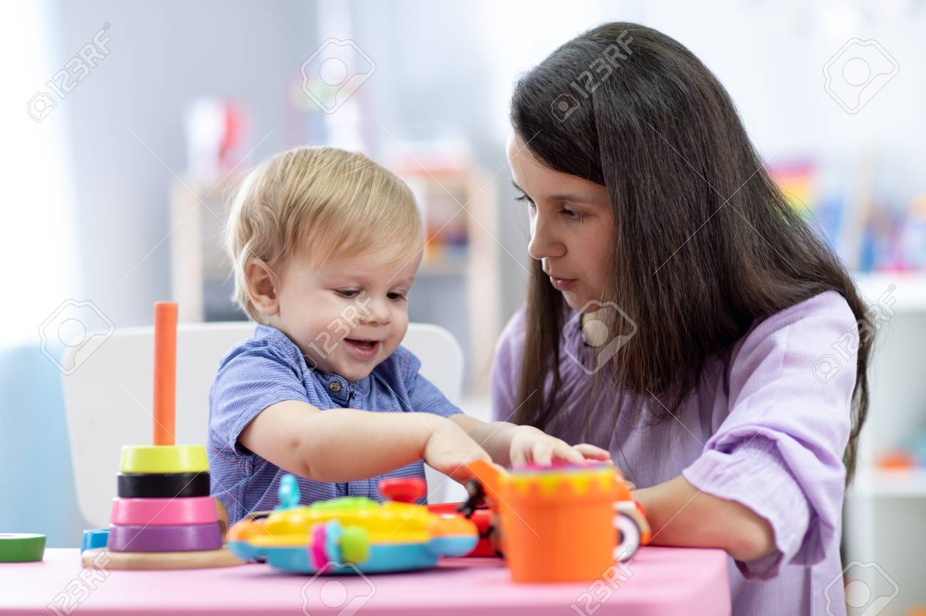 Cute woman with child playing with plastic blocks at home or kindergarten - 121461925