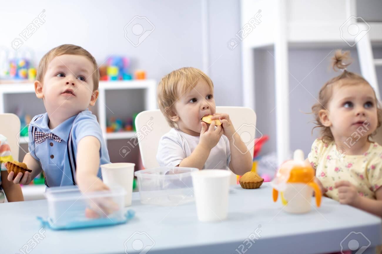 babies children toddlers have dinner in nursery or kindergarten - 122594448