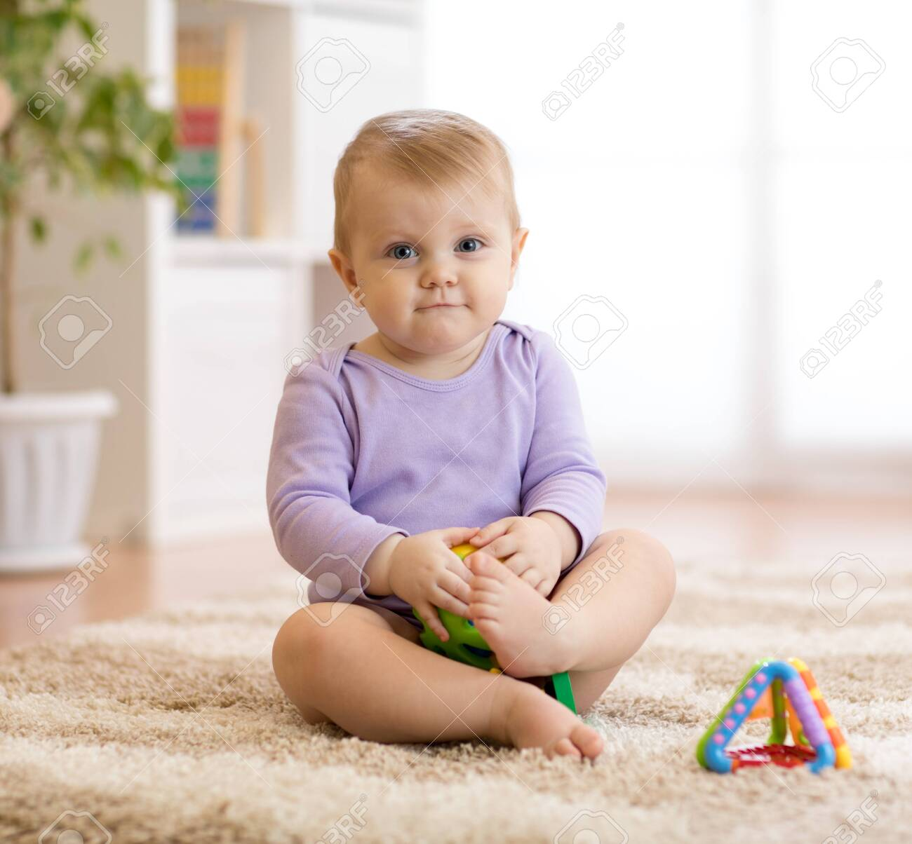 cute funny baby sitting on carpet at home - 124452355