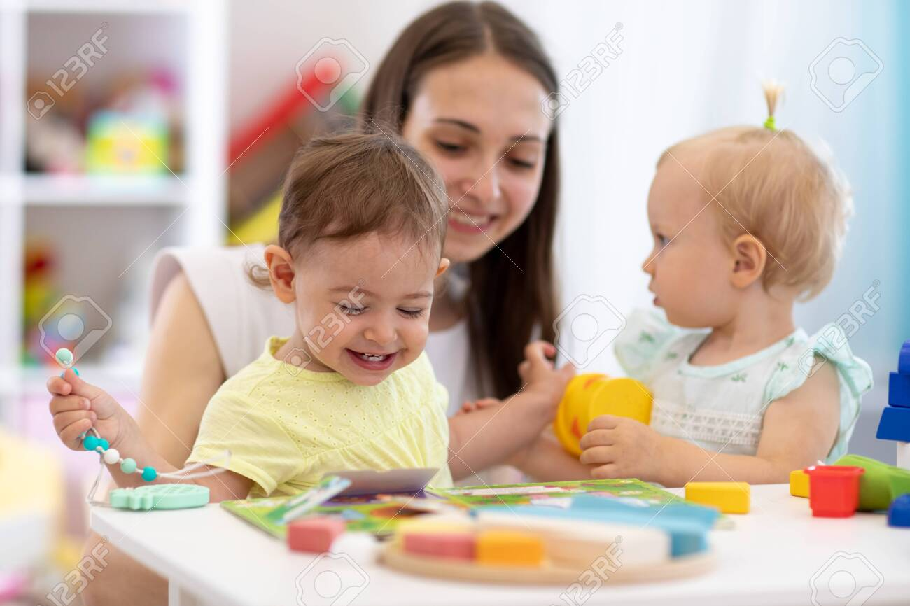 Nursery teacher and cute babies playing with toys in creche - 131982844