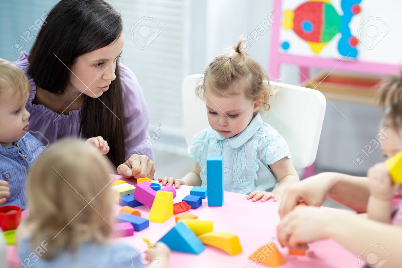 Kids toddlers playing with color blocks on lesson in classroom in kindergarten - 138983917