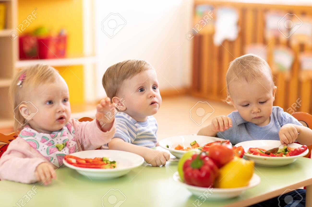 Kids eating in kindergarten or day care centre - 135036713