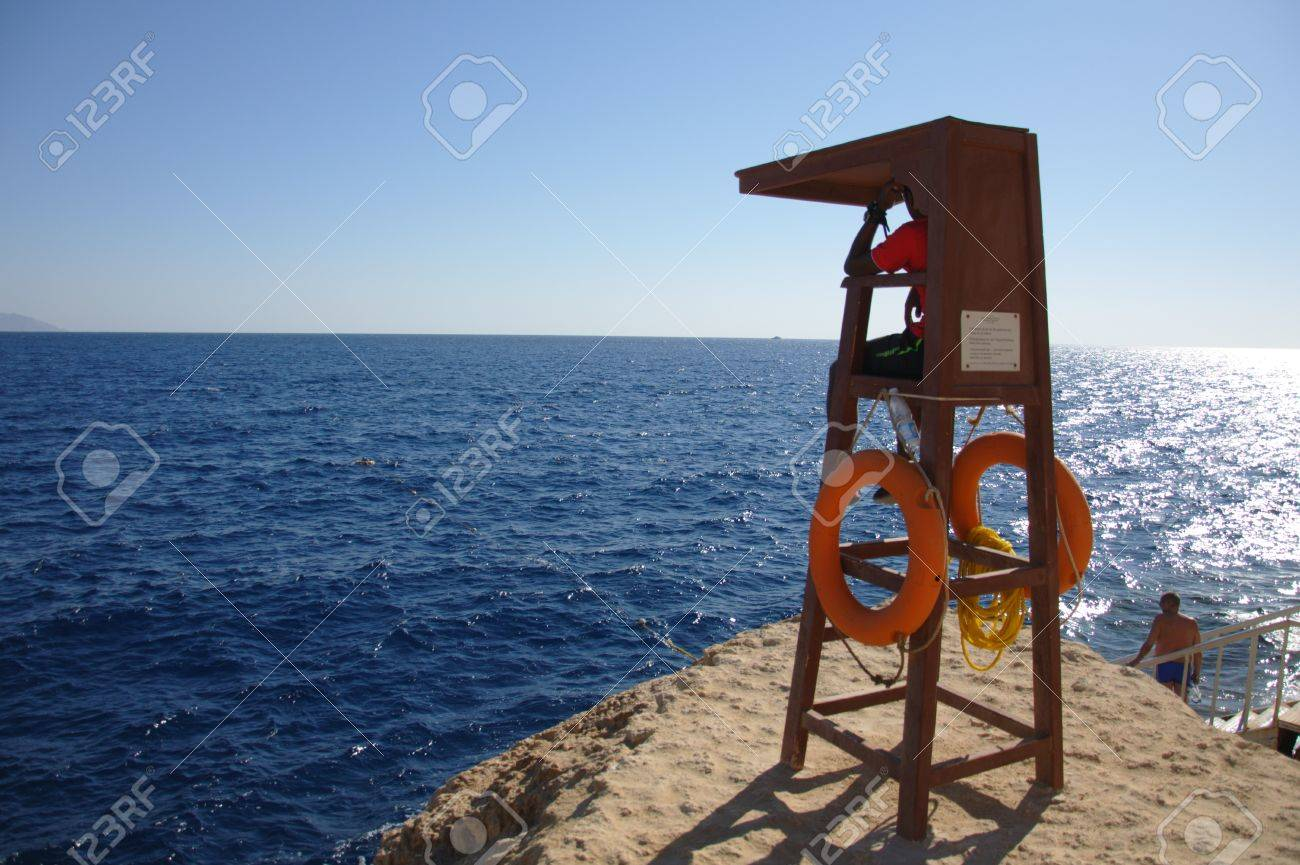 SHARM EL SHEIKH, EGYPT - NOVEMBER 30: Unidentified lifeguard watch the beach for tourists snorkeling on November 30, 1010, the same day as four Russian holidaymakers were badly injured at the same coastline in Sharm El Sheikh, Egypt. Stock Photo - 8448674