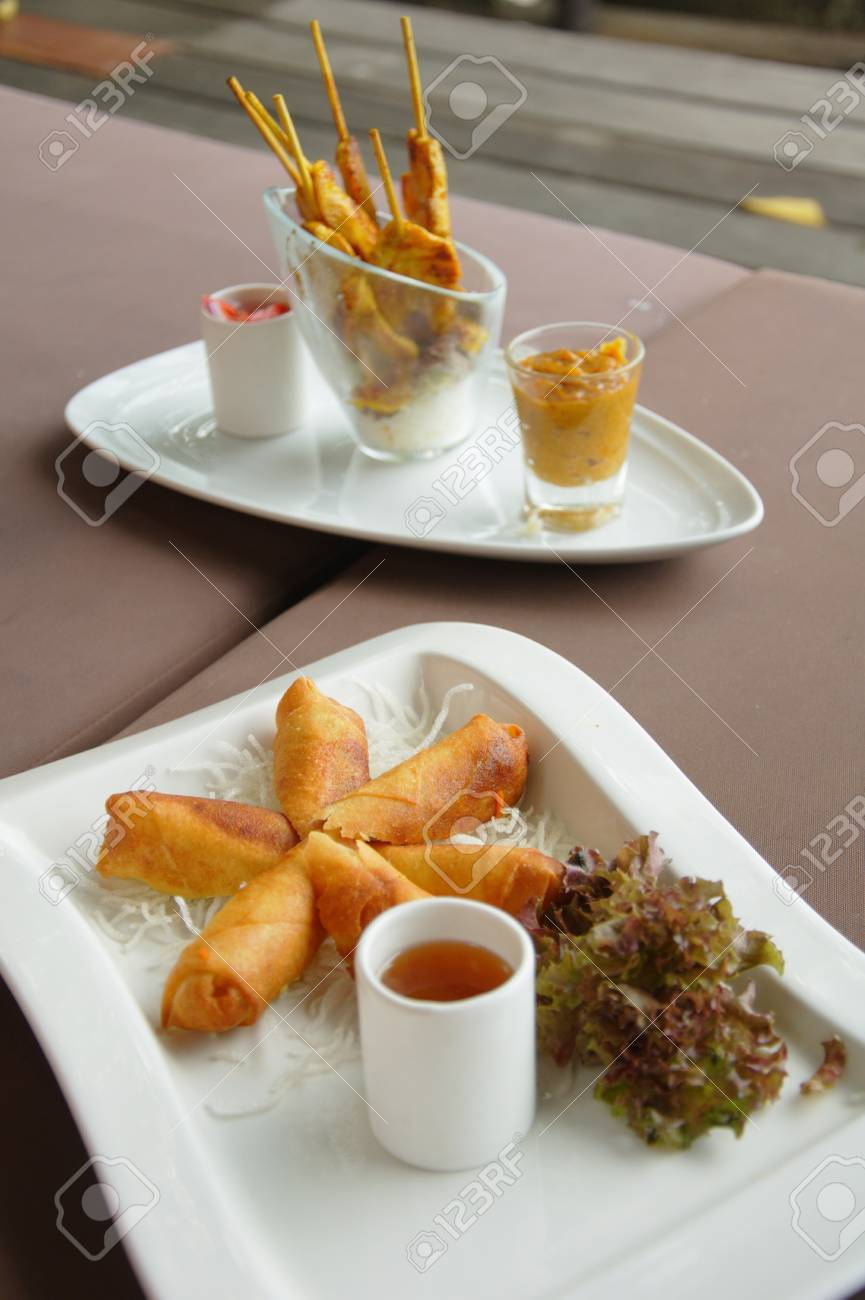 Spring rolls on a plate with a chicken satay plate in the background on a resort at Lamay, Koh Samui in Thailand Stock Photo - 10035579