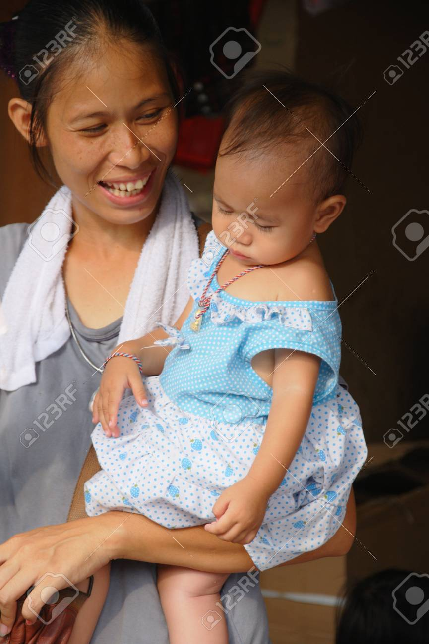 Unknown mother with child at Chatuchak market in Bangkok, Thailand. The mother has a towel as it was a very hot and humid day. Stock Photo - 10007365