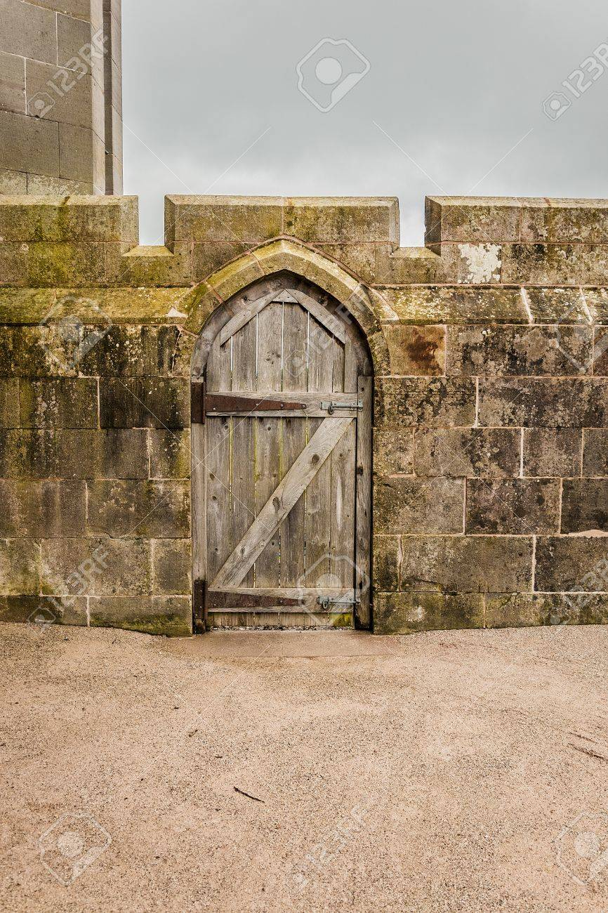 Old Wooden Door In A Stoned Wall Castle Wall Stock Photo, Picture ...