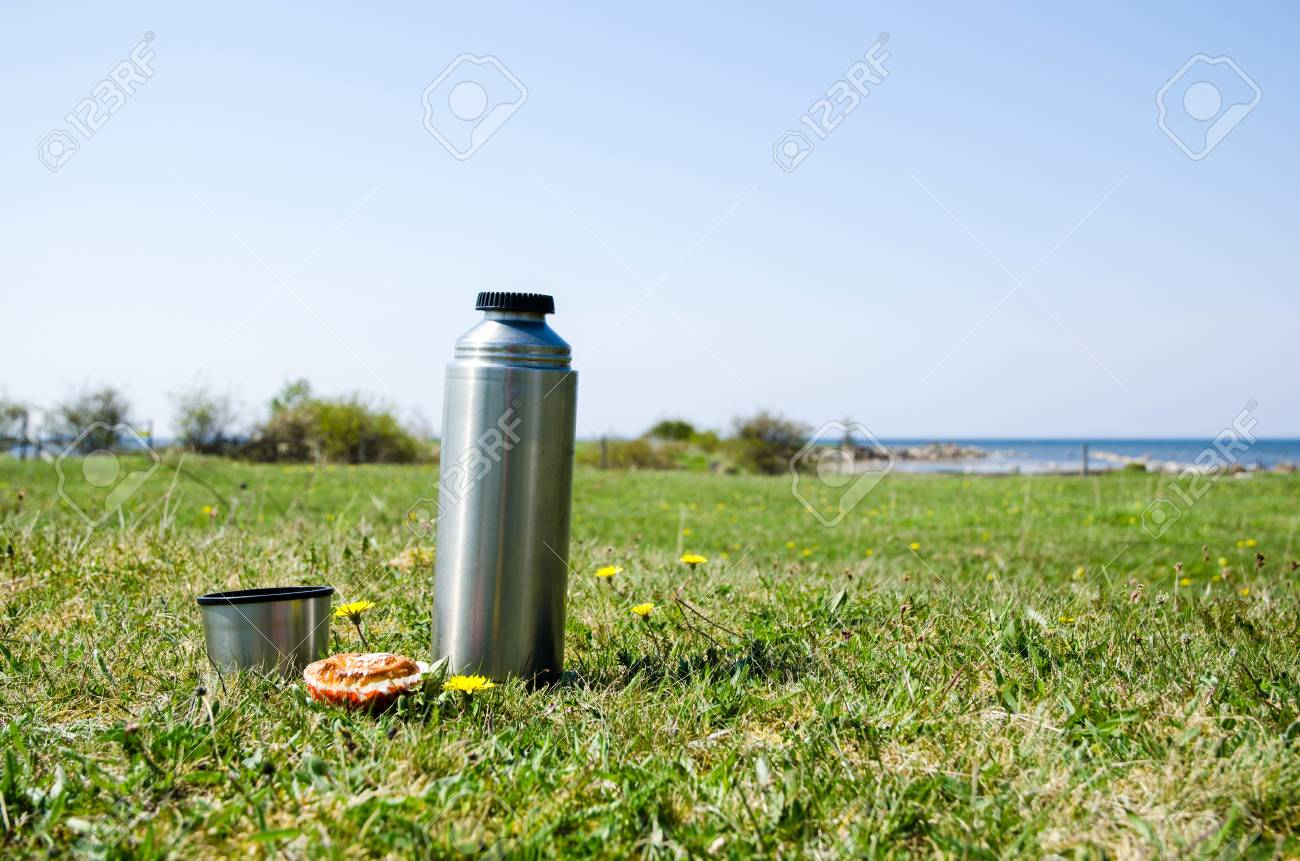 Thermos with bread on a grass field at the coast in springtime Stock Photo - 19839364