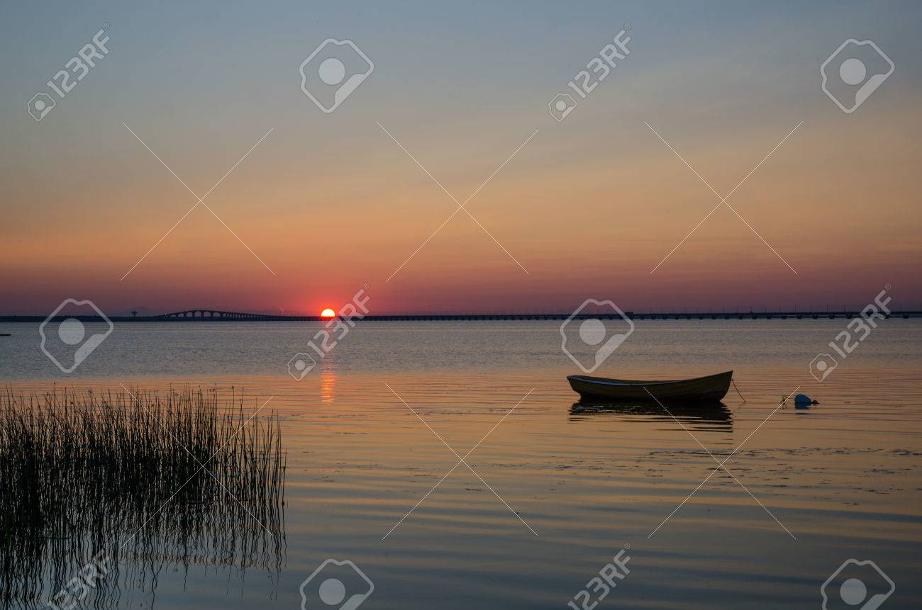 Lone rowboat in calm water at sunset with the Oland Bridge in Sweden as background Stock Photo - 30571795