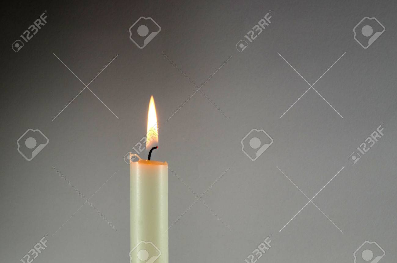One burning white candle at a grey background Stock Photo - 33124935