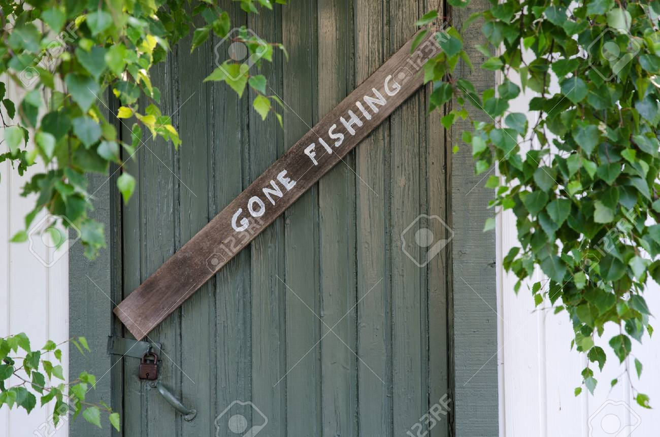 Gone fishing sign at an old green door and green leaves Stock Photo - 43344999