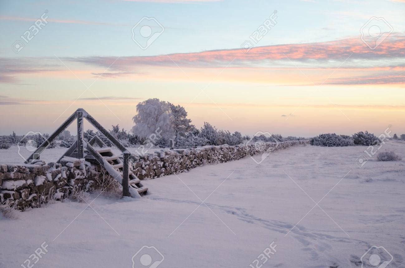 Dawn at a winter landscape with a stile by stone wall Stock Photo - 52343475