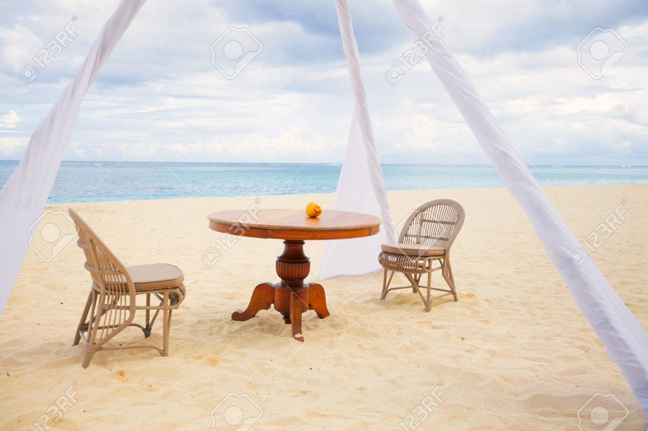 Mesa de comedor privada y sillas de mimbre para una cena romántica para  parejas de luna de miel en una playa tropical