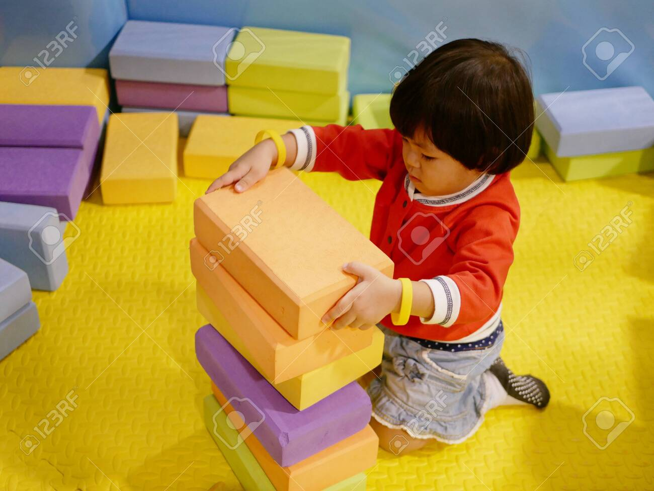 Little Asian baby girl stacking up foam building bricks / blocks at an indoor playground - playing foam blocks helps develop children's fine motor and logical thinking skills - 125869795