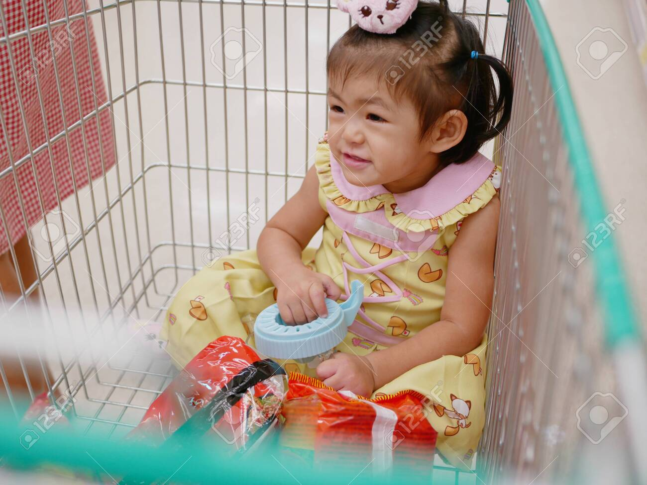 Little Asian baby girl sits in a cart, enjoys doing shopping with her mother - doing errands with toddler - 129808057