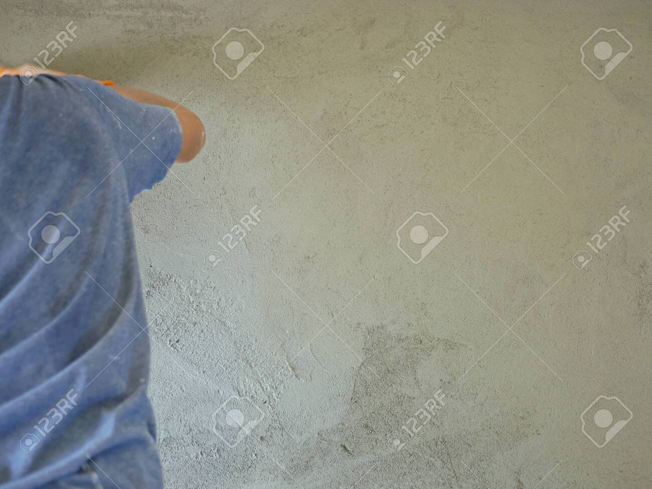 A house wall being plastered and getting close to a completion by a construction worker - 129881568