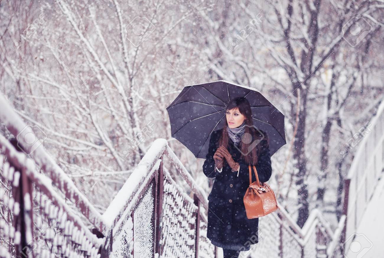 Beautiful Young Woman With Umbrella In Snowfall Toned Image Stock
