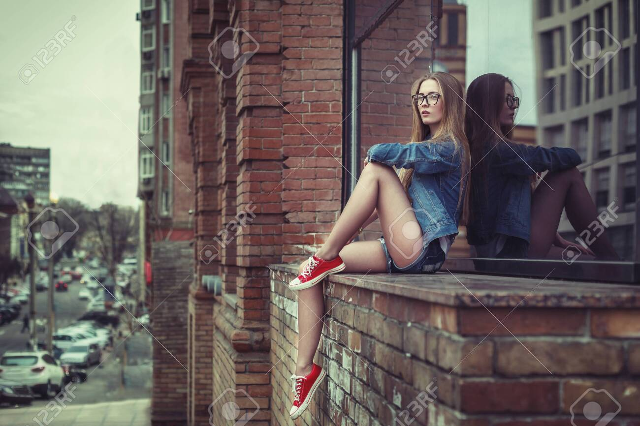 Outdoor lifestyle portrait of pretty young sitting girl, wearing in hipster swag grunge style urban background. Retro vintage toned image, film simulation. - 122913381