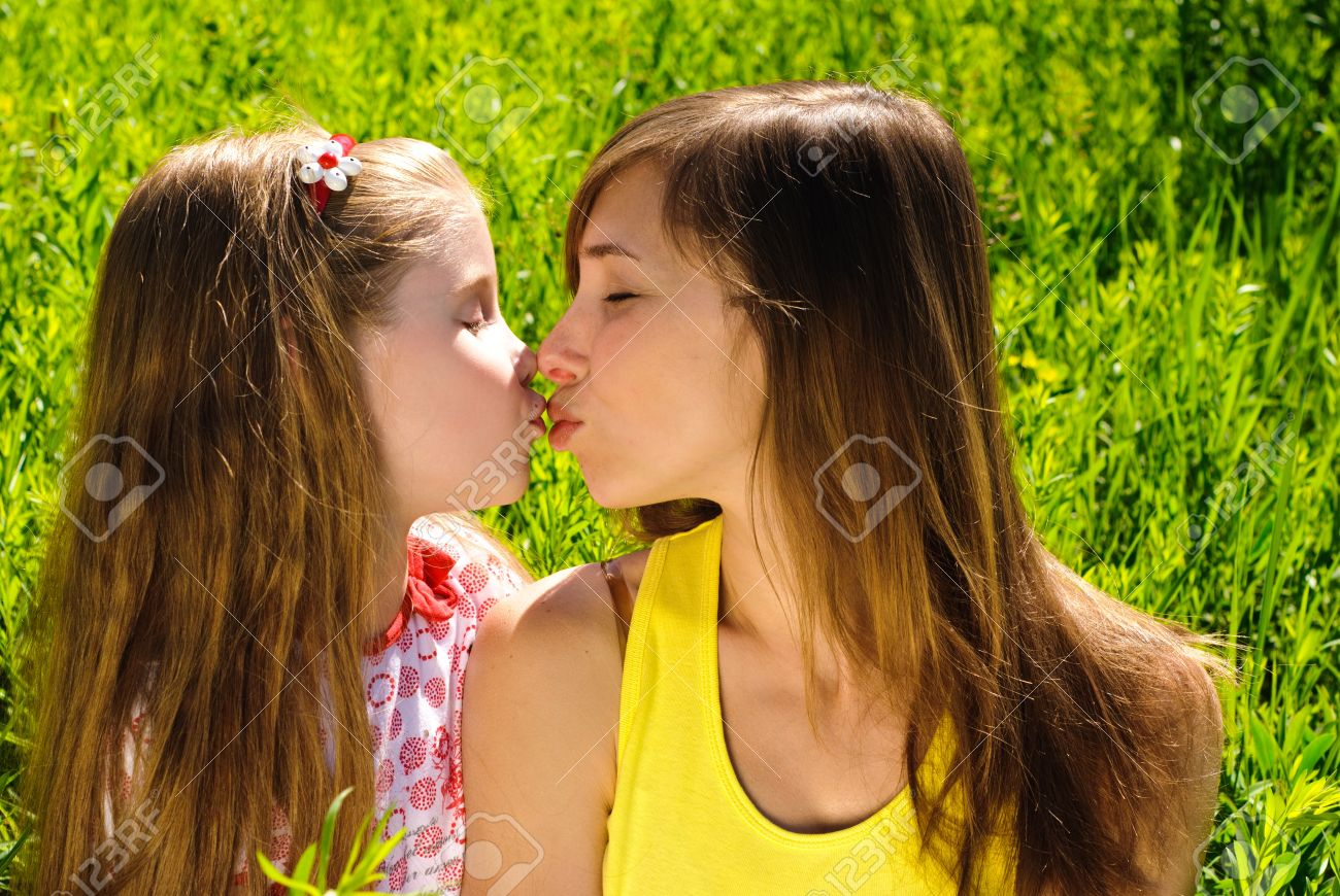 Kissing young mother and little daughter outdoor. Sunny summer day. Stock Photo - 10844521