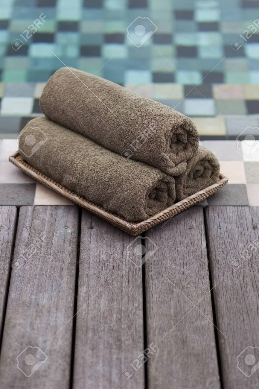 Three grey towels rolled near swimming pool.