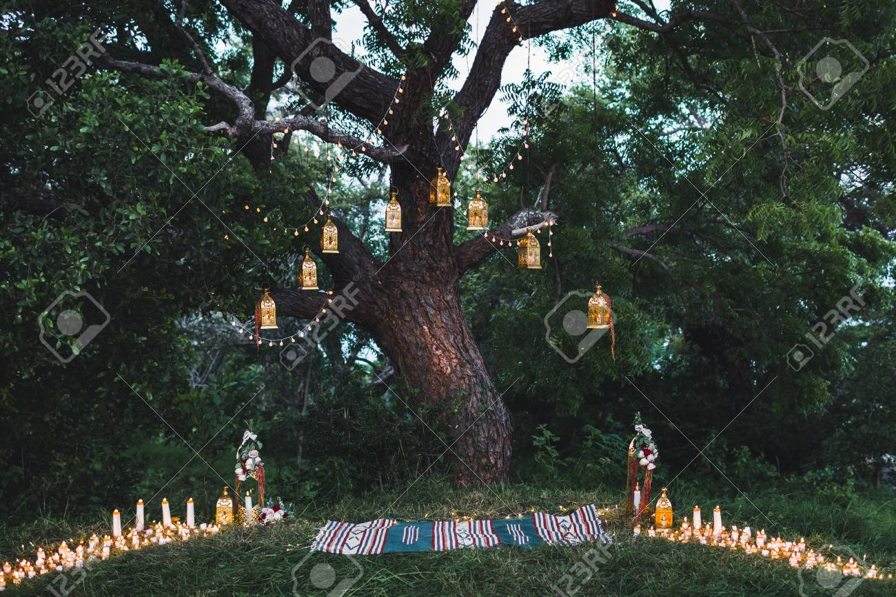 Night wedding ceremony with a lot of candles and vintage lamps on big tree - 62343370