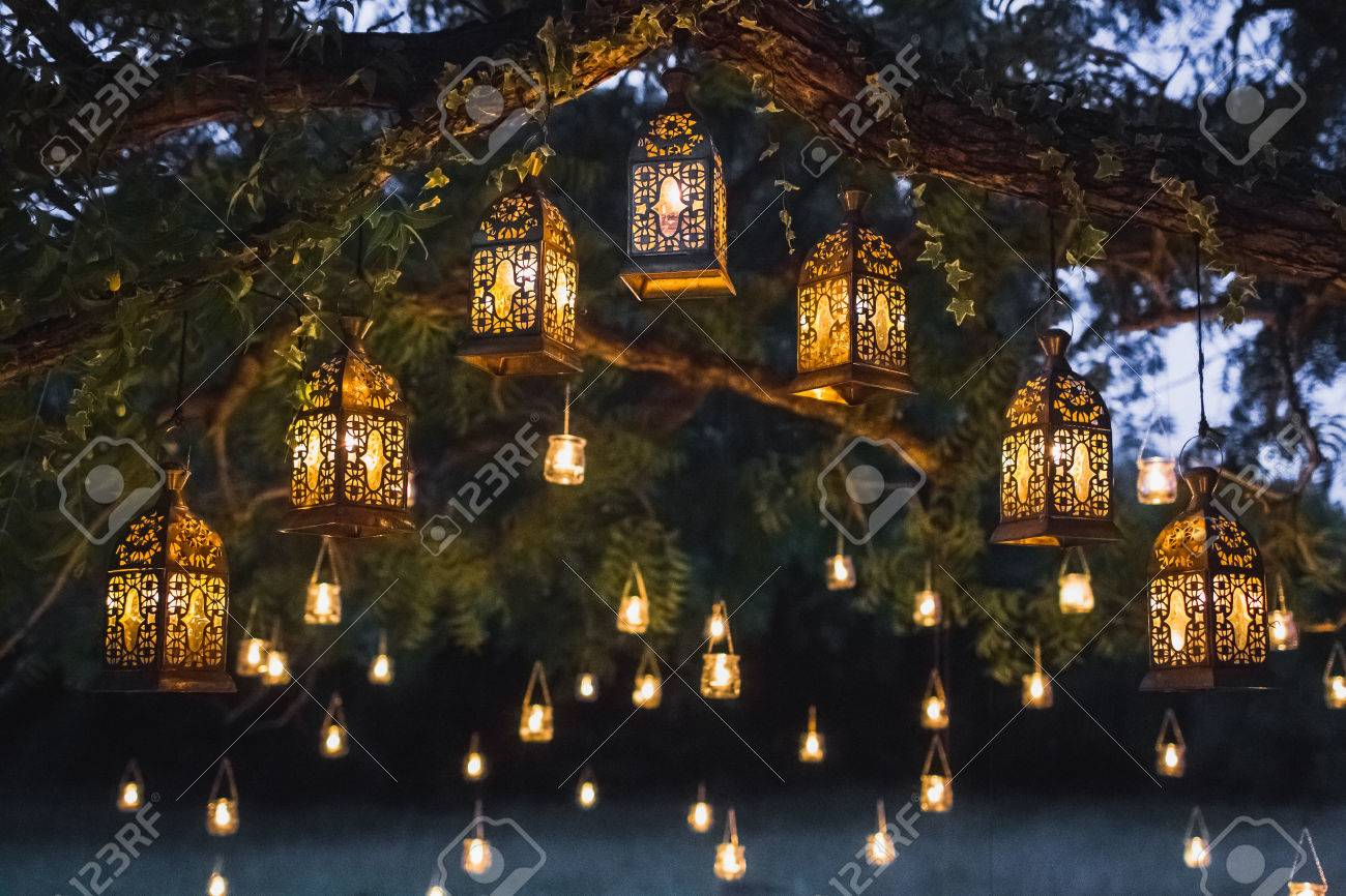 Night wedding ceremony with a lot of vintage lamps and candles on big tree - 81792067