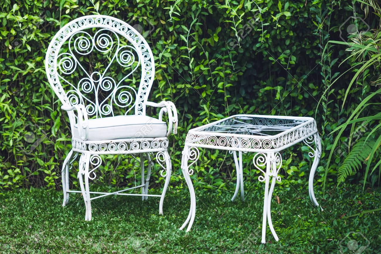 Vieux meubles anciens en jardin avec un fond vert naturel. Chaise et table  en métal blanc, style européen à l\'ancienne
