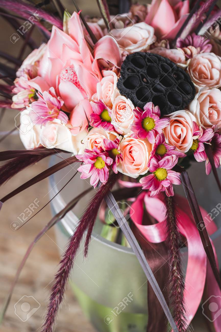 wedding bouquet in boho style with pink silk ribbons roses