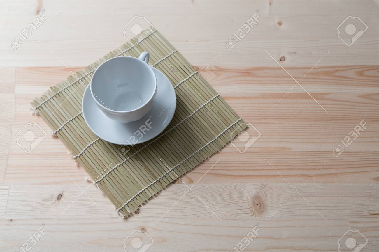 One Pure White Ceramic Cup And Saucer Stands On A Wooden Table