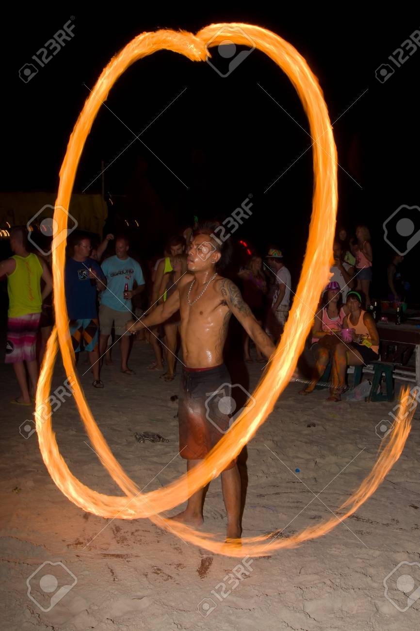 PHANGAN - JANUARY 08 : There are about 10,000 people every month at this Phangan beach Full moon party, on January 08, 2012 in Koh Phangan , Thailand . Fire dancer on a beach - blur Stock Photo - 11867991