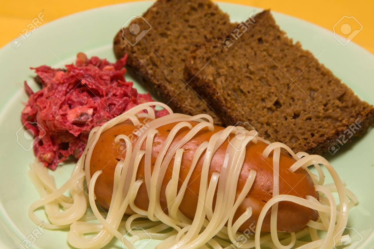 Pasta pierced sausage on the green plate Stock Photo - 13567259