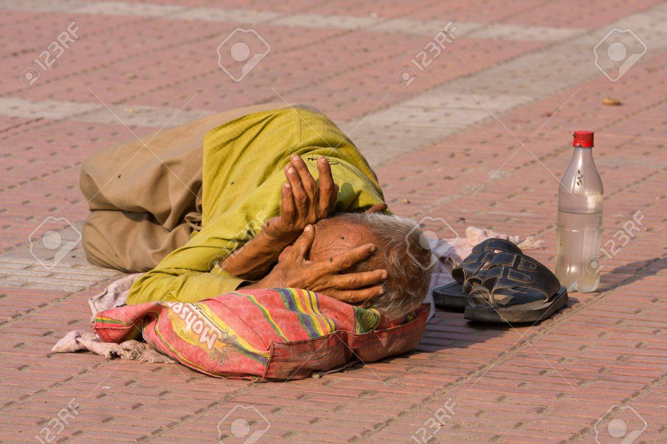 HARIDWAR, INDIA - NOV 8: An unidentified homeless man sleeps on the sidewalk near the River Ganges on November 8, 2012 in Haridwar, India. Poor Indians flock to Haridwar for charity. Stock Photo - 19389078
