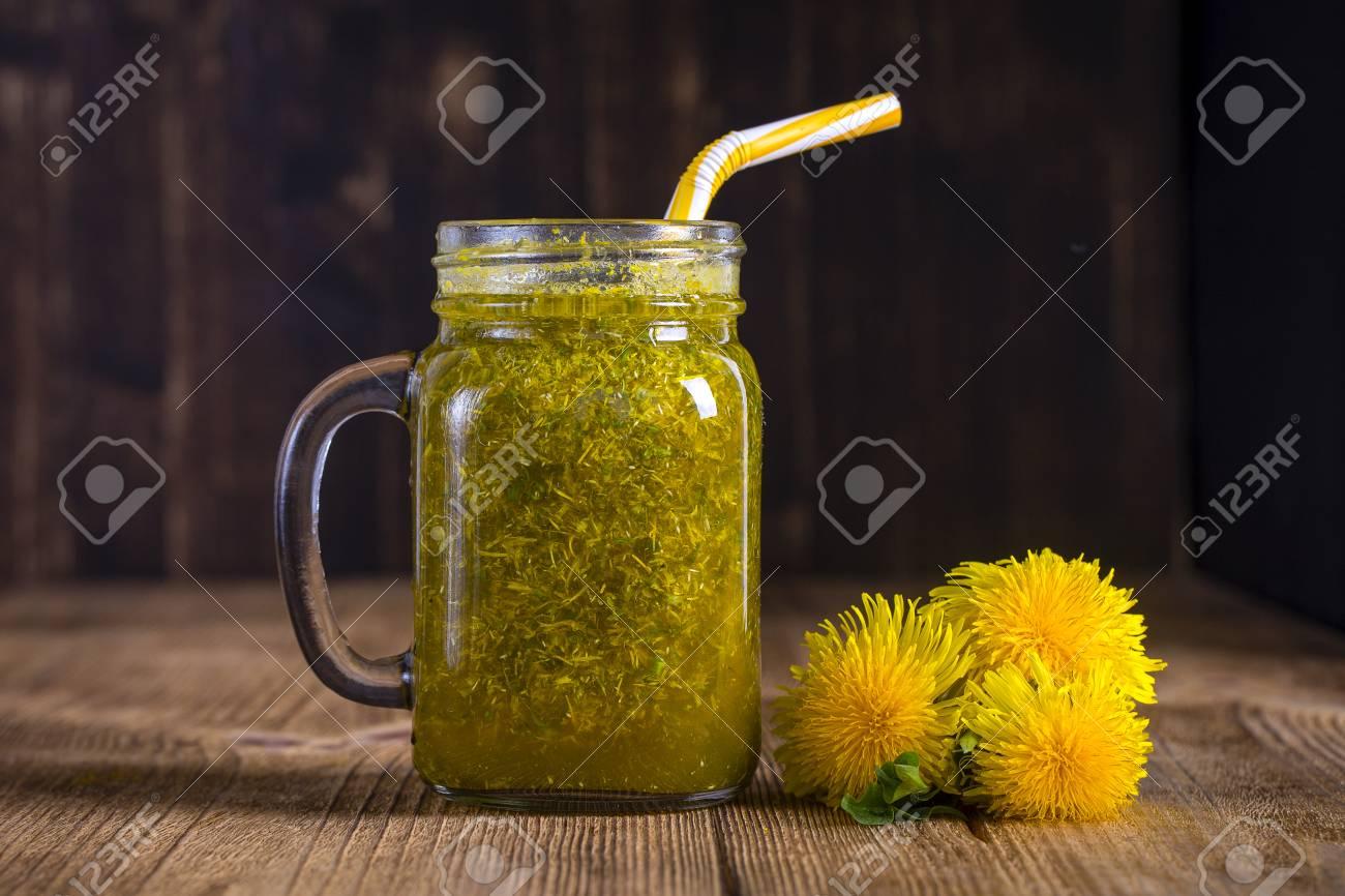 Dandelion yellow flower tea drink in glass mug on wooden table dandelion yellow flower tea drink in glass mug on wooden table close up concept mightylinksfo