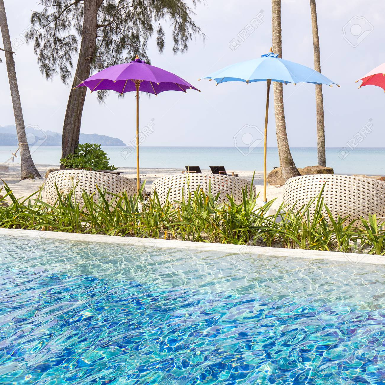 Swimming pool, umbrellas and deck chairs on the sand beach near..