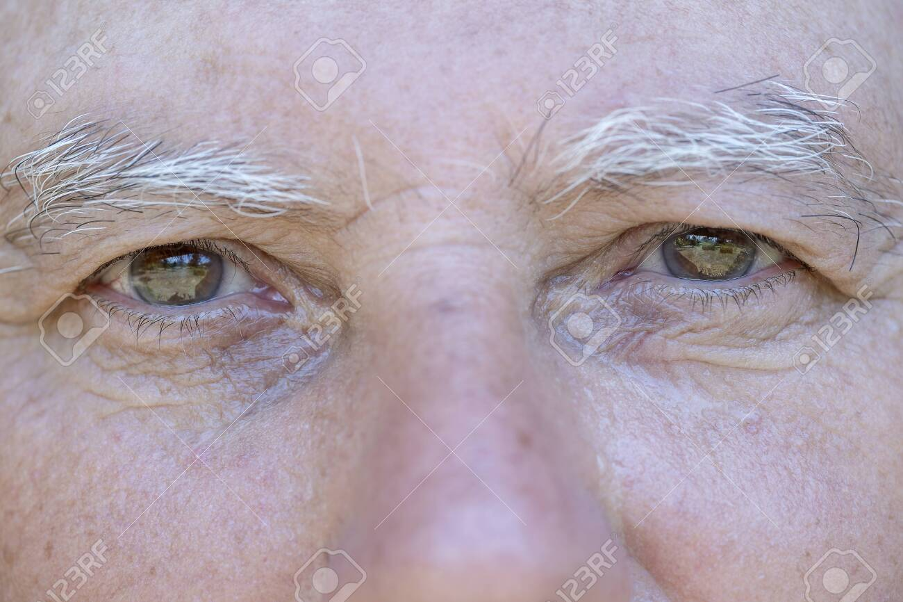 Close up eye of caucasian old man. Portrait of old man outdoors. Caucasian male face background, close up eyes, macro - 123075019