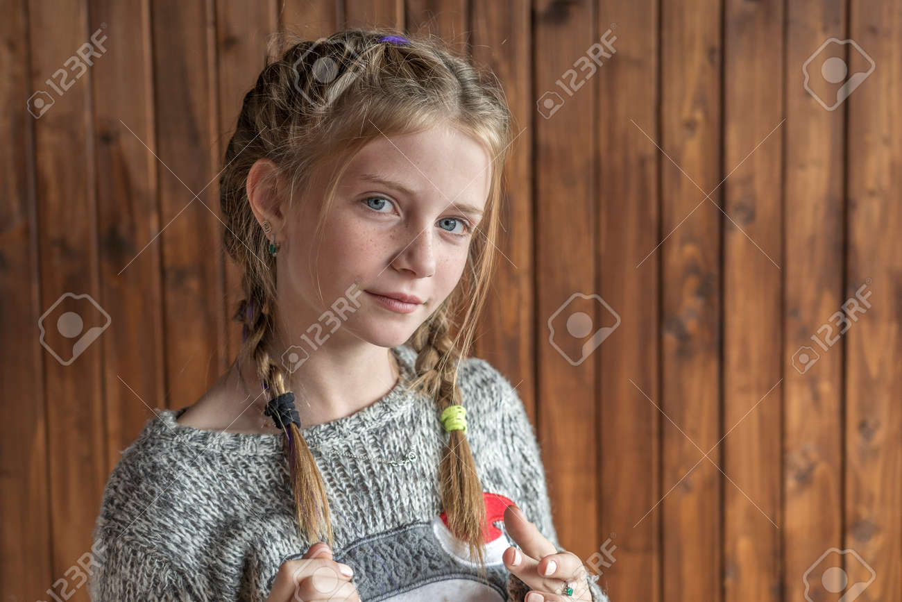Beautiful blonde young girl with freckles indoors on wooden background, close up portrait - 151920900