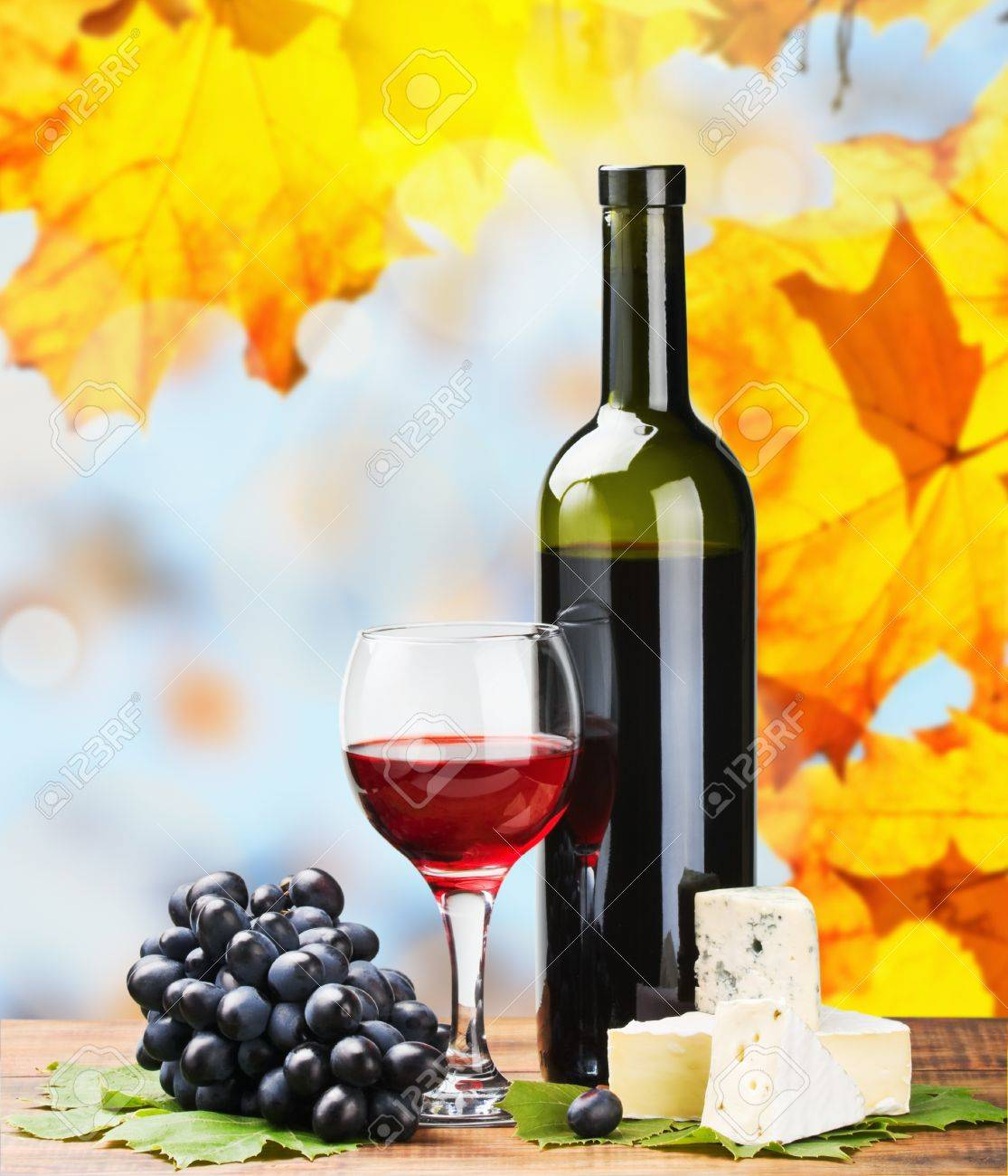 bottle, glass of red wine and assorted cheeses on a background of autumn leaves Stock Photo - 15281519