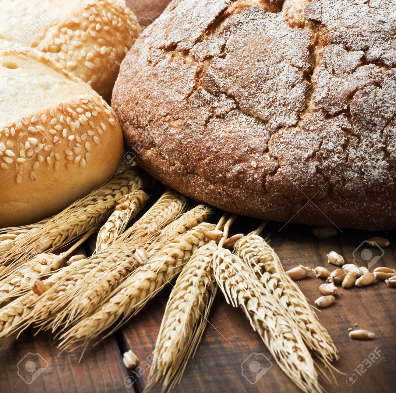 fresh bread and rolls with ears of wheat on the table Stock Photo - 15789881