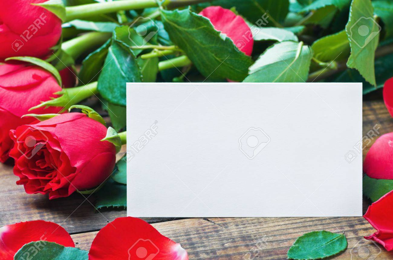 red roses and white card with a place for a congratulatory text on a wooden table Stock Photo - 16902036