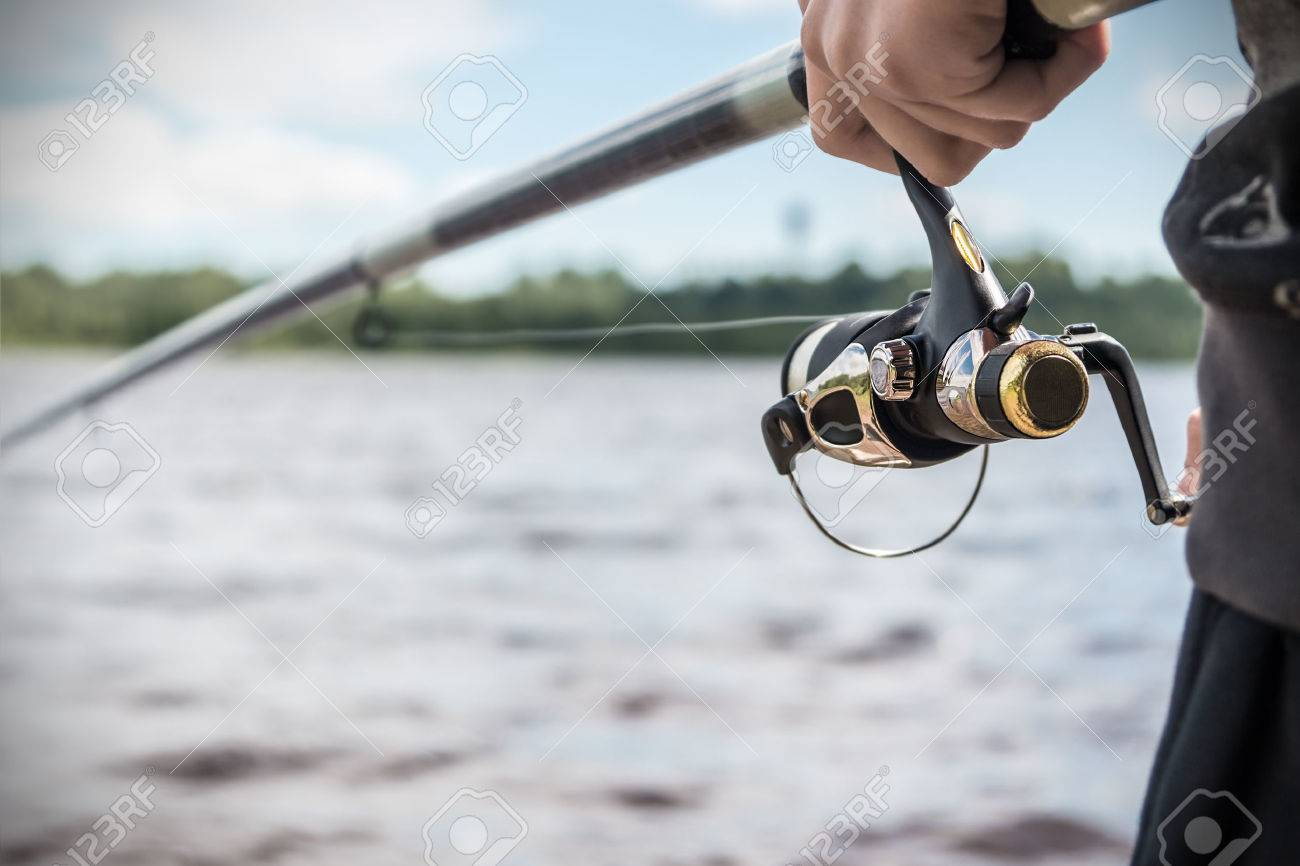 hand holding a fishing rod with reel. Focus on Fishing Reels - 43166988