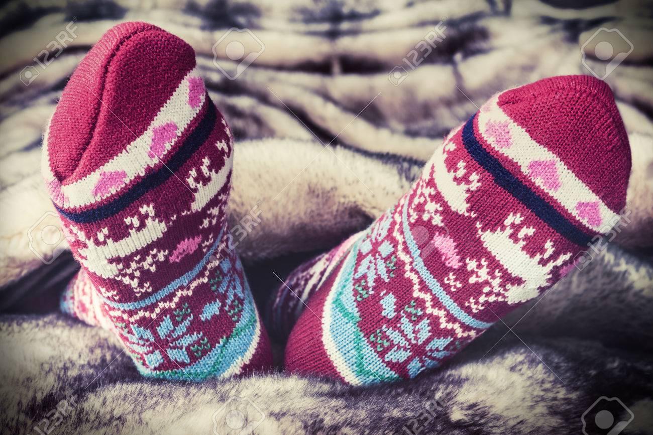 Female legs in Christmas socks under a blanket of fur. toning image - 44715360