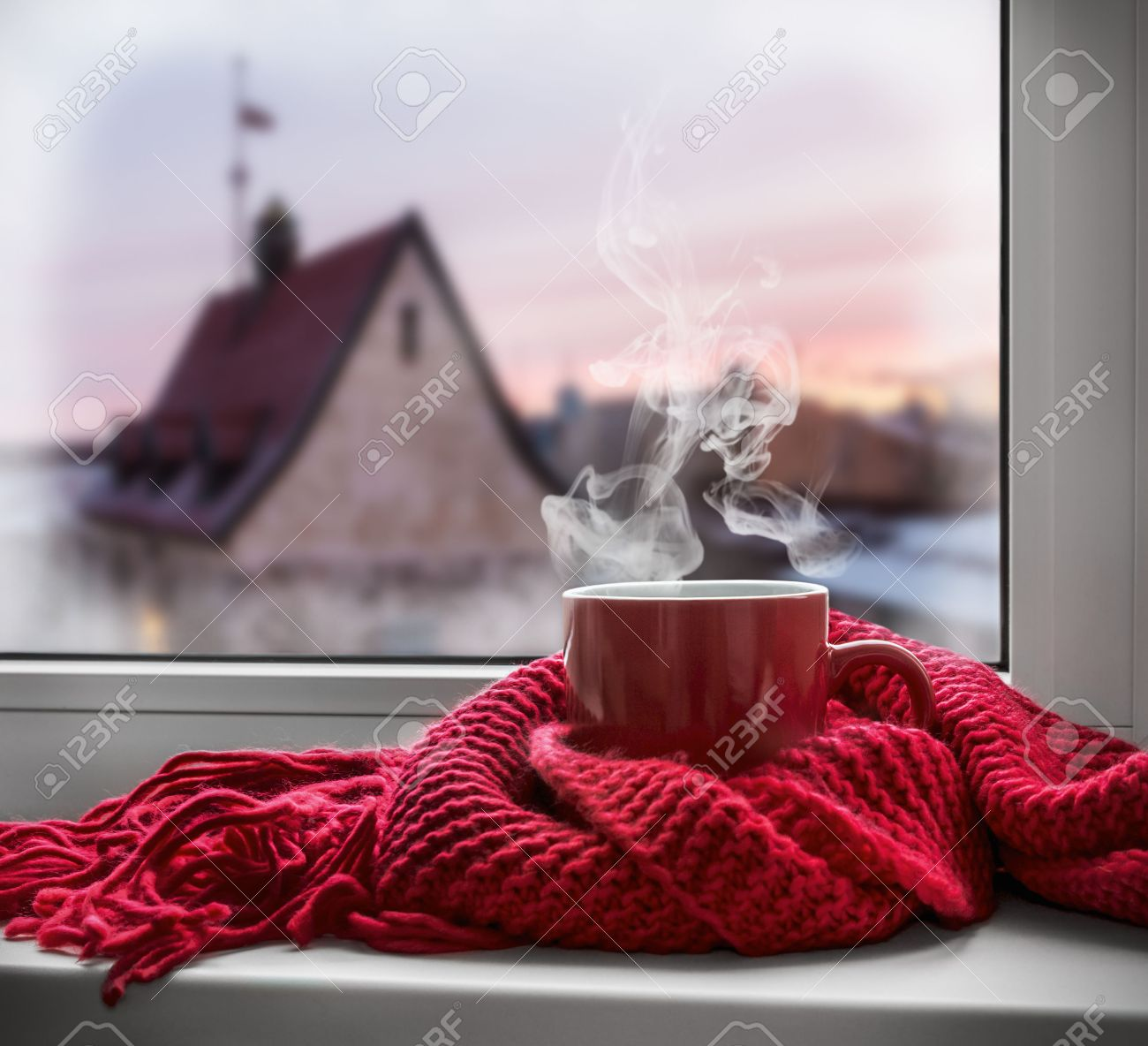 cup with a hot drink on the windowsill in the background of a winter city. Focus on the edge of the cup - 44713977