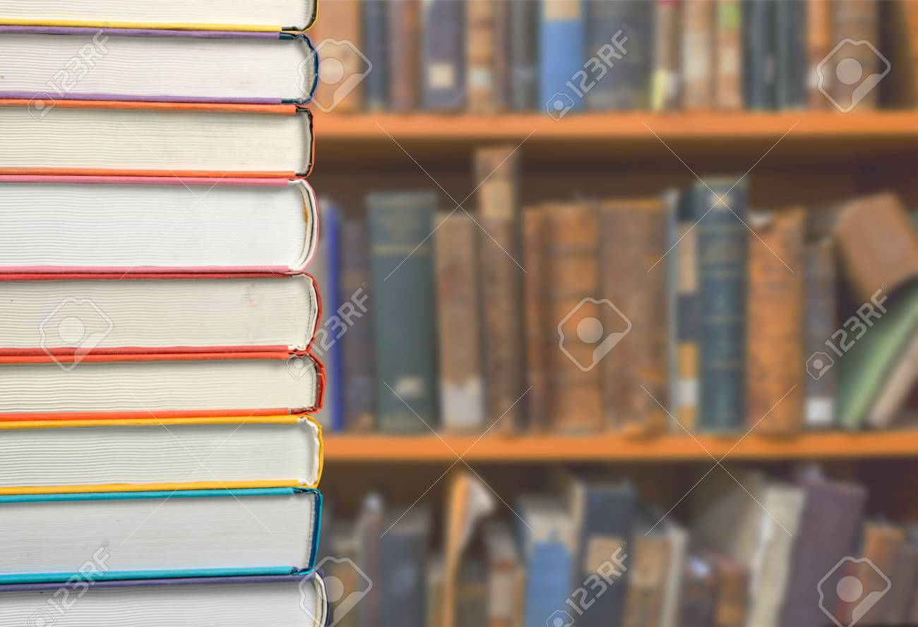 Book Stack On Wood Desk And Blurred Bookshelf In The Library
