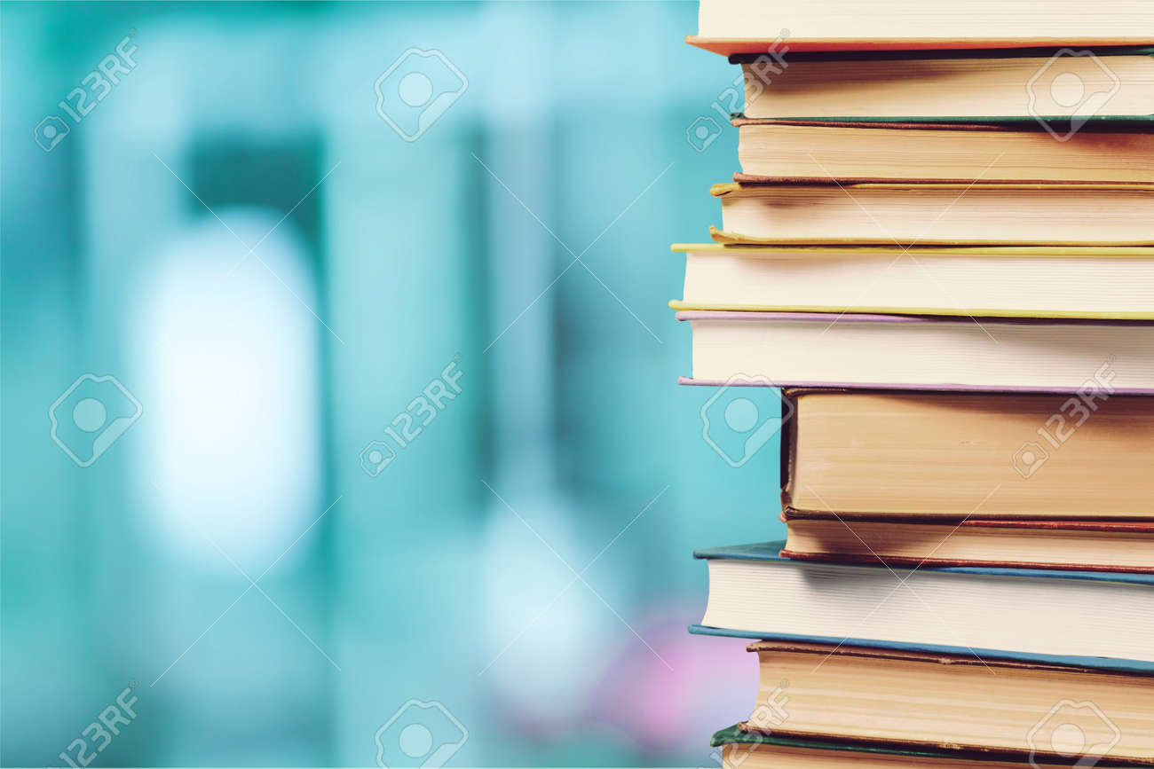 Stack of colorful books on blurred background - 123948647