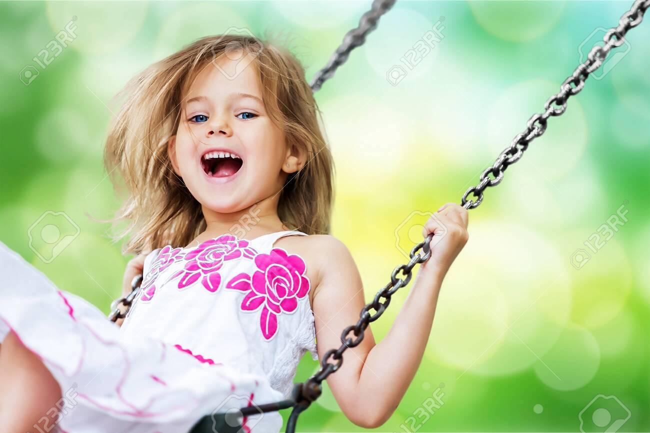 Little child blond girl having fun on a swing - 124269562