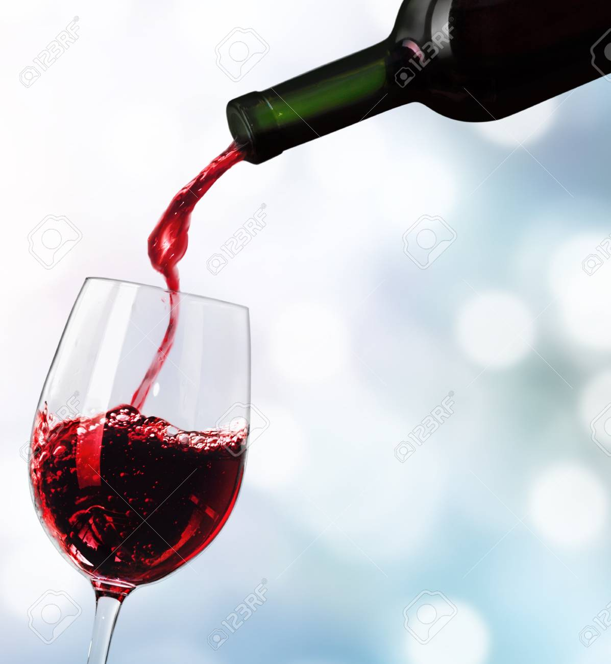 Red wine pouring in glass isolated on white background - 124596563