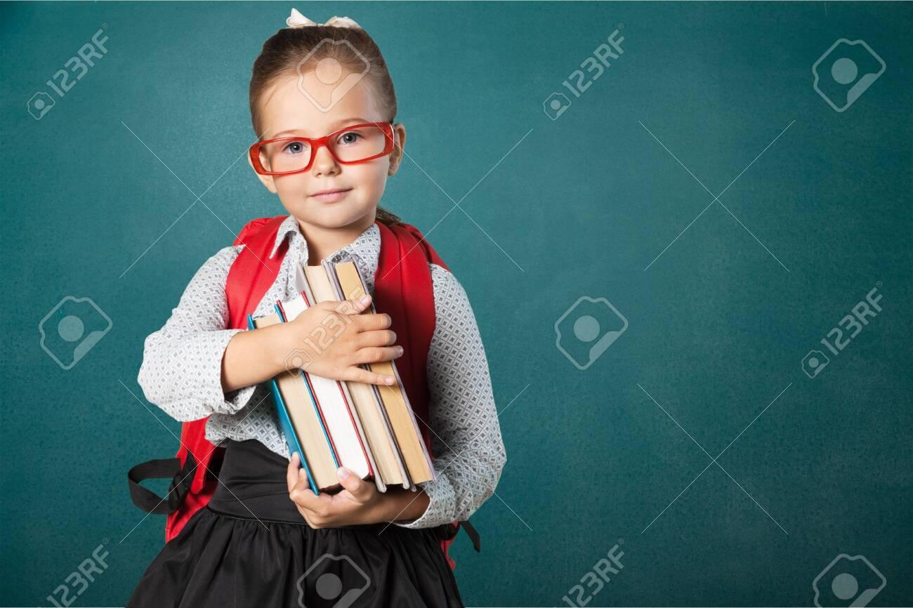 Cute little schoolgirl in glasses on blackboard - 124300888