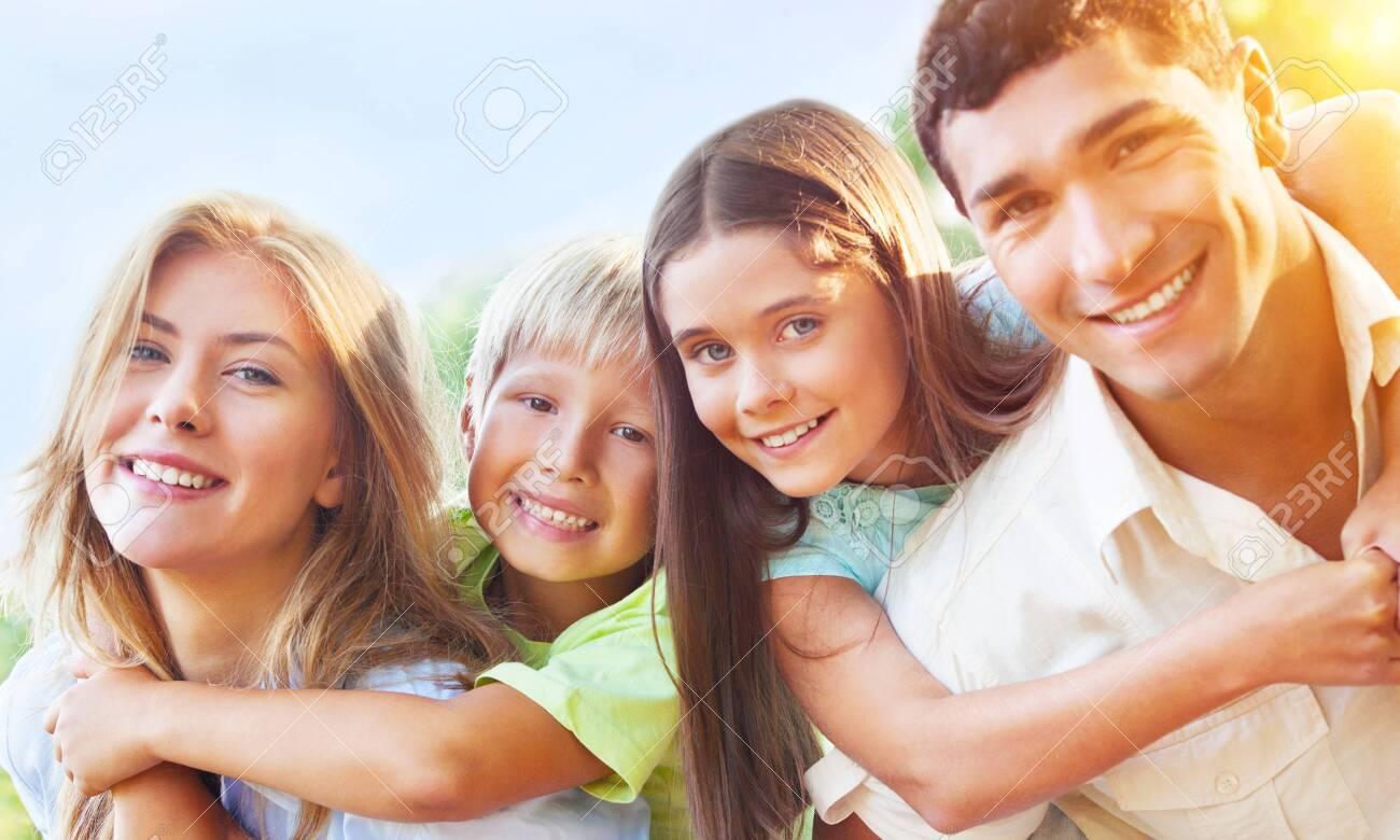 Parents Giving Children Piggybacks In Countryside - 124301555