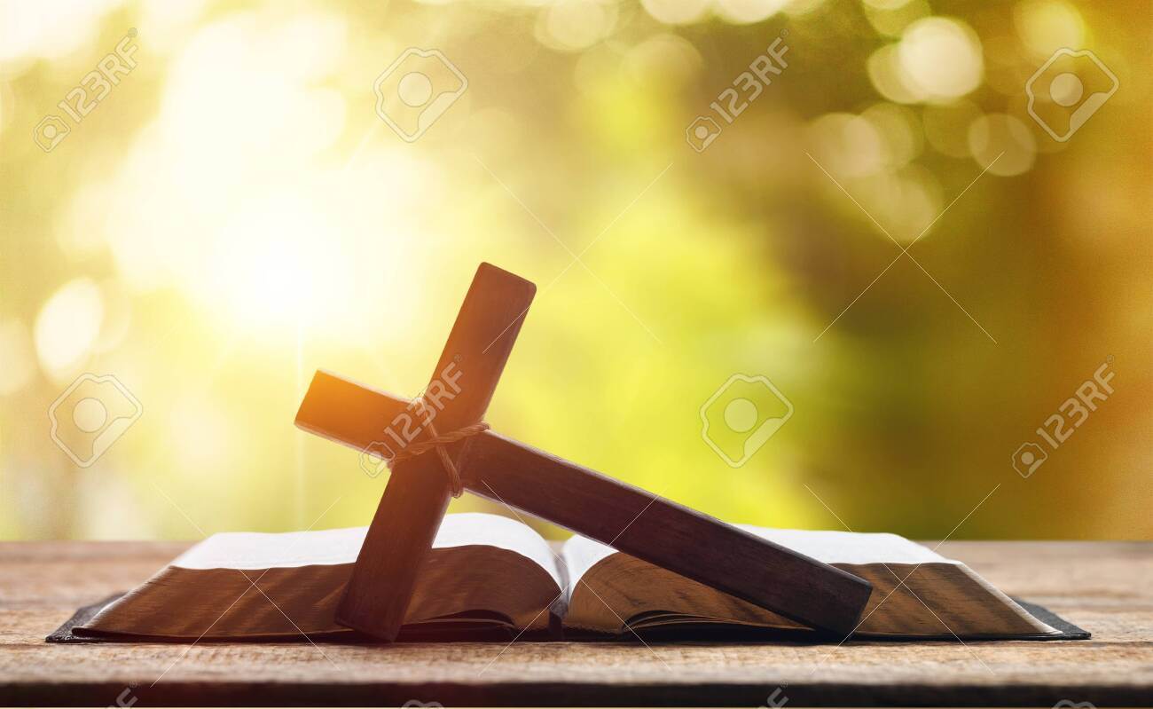 Holy Bible on the background of the Christian cross and the life-giving divine light. The hope of mankind for salvation. The way to God through prayer. The Resurrection and Rapture of Jesus. - 125050269