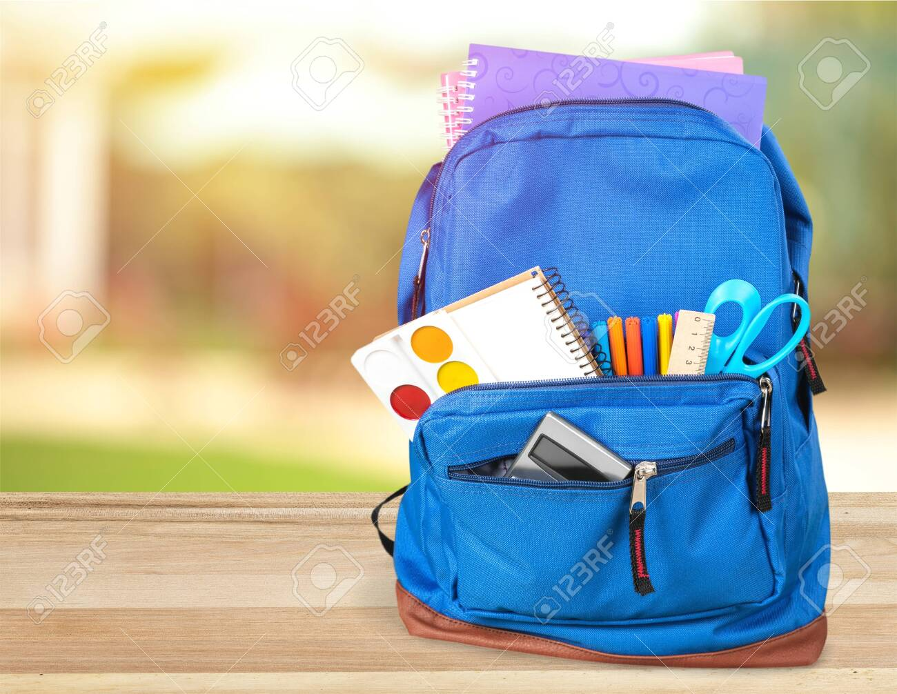 Colorful school supplies in backpack on wooden background - 125222423
